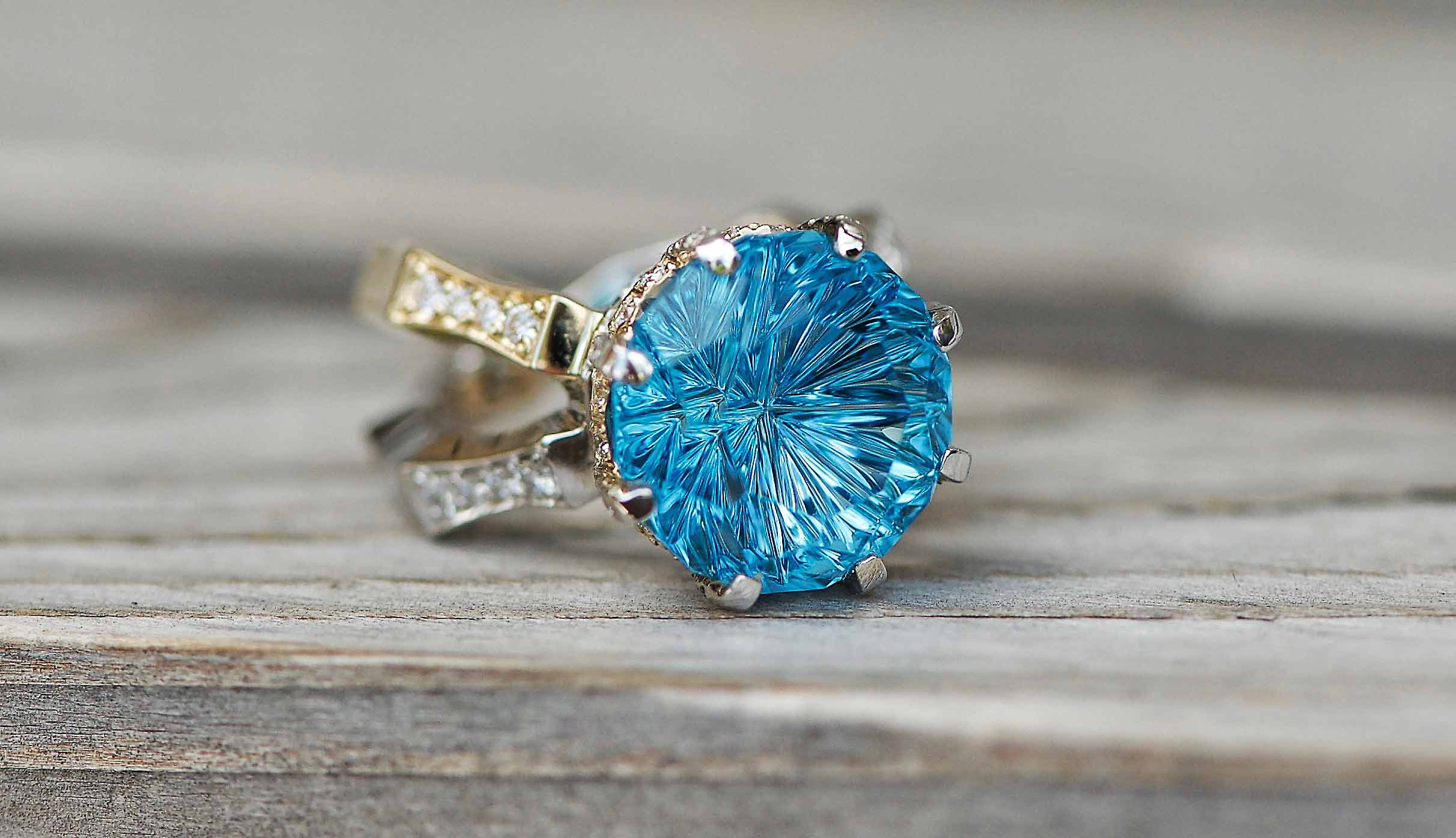 StarBrite™ cut Blue Topaz by John Dyer & Co. in a ring designed by Ryan Masters for Midwest Jewelers and Estate Buyers, made in yellow and white gold and diamonds.